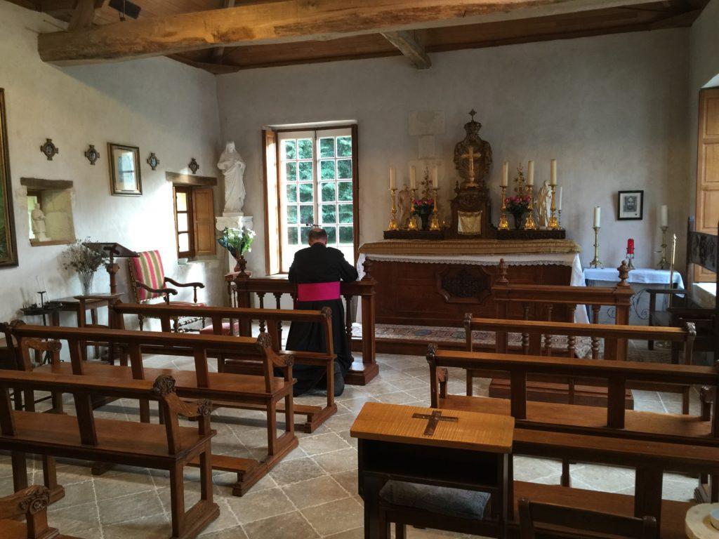 Bishop Sanborn prays in a chapel in Loches